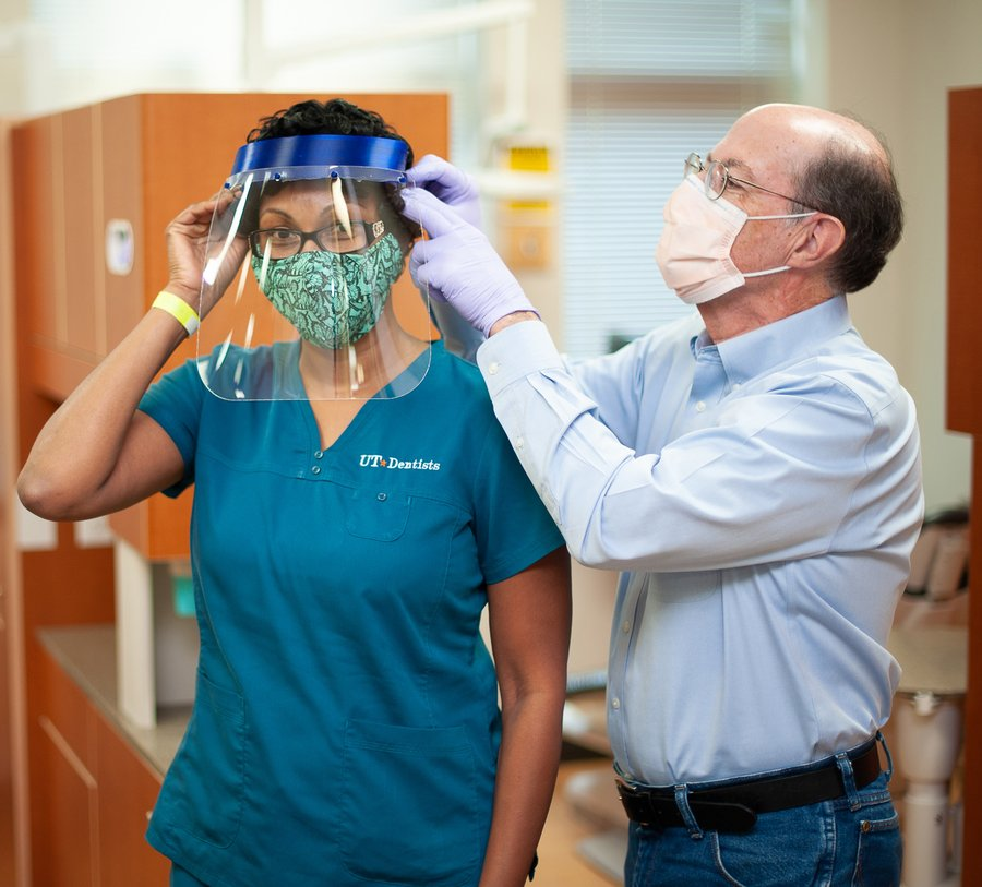 Dr. Scott Makins adjusts a face shield for Dental Assistant Toyia Rose. The shield is one made by his niece, a STEM teacher in Dallas.
